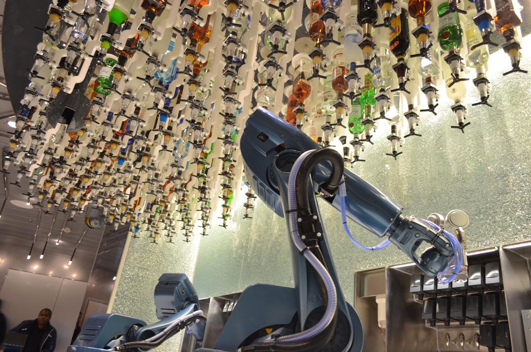 Uno de los atractivos del barco son los dos primeros camareros robots del mundo, a quienes los invitados encargan cócteles mediante unas tablets que se reparten entre las mesas. En la imagen los dos artilugios preparando cócteles con las botellas que están suspendidas en el techo.