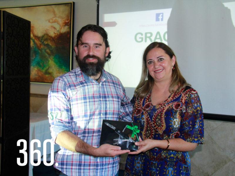 El conferencista Alejandro Argüelles Flores recibió un regalo de Ana María Melo presidenta del Club de Jardinería Rosal.