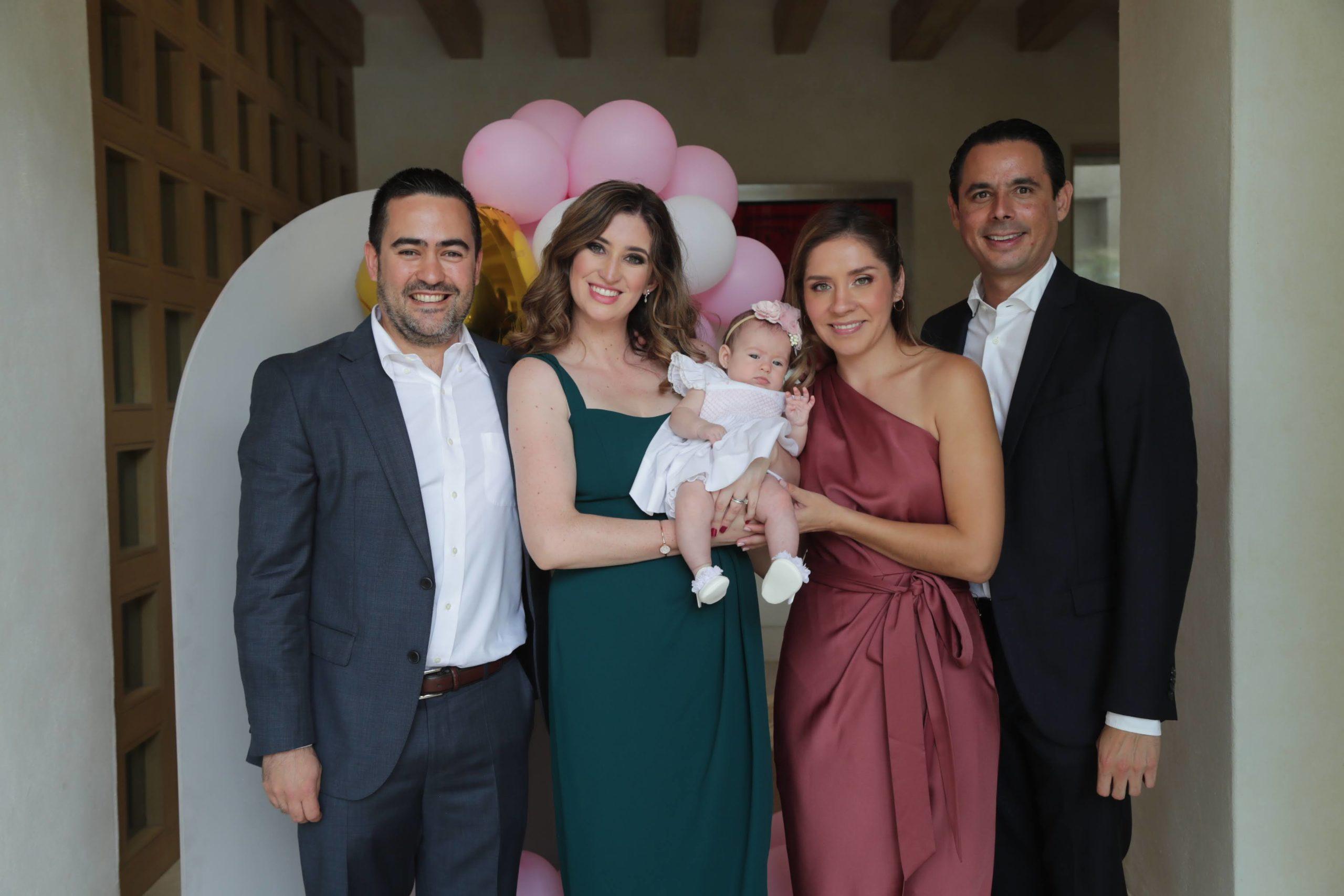 Eugenia con sus papás y padrinos.