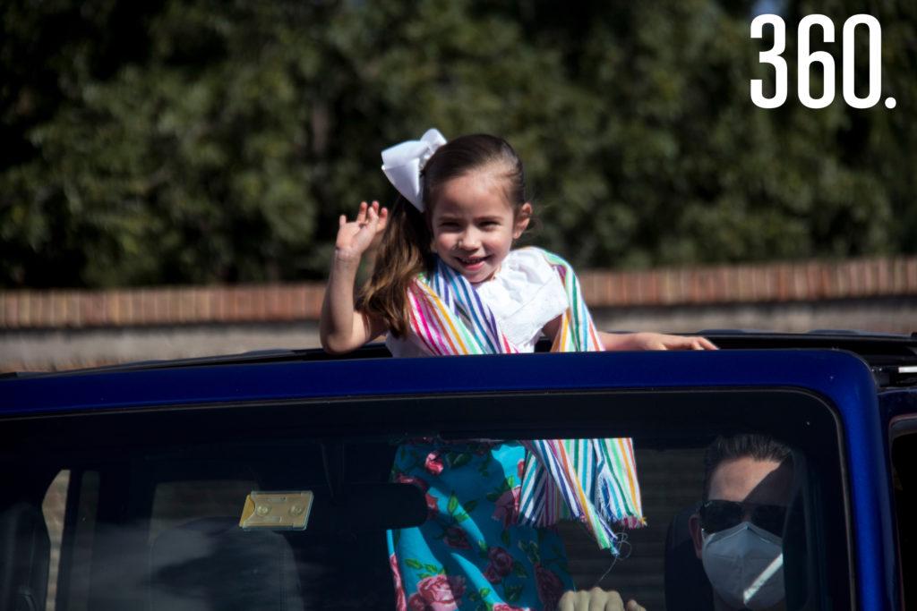 Miranda Ramos saluda a sus maestras desde el techo de su Jeep acompañada por su papá.