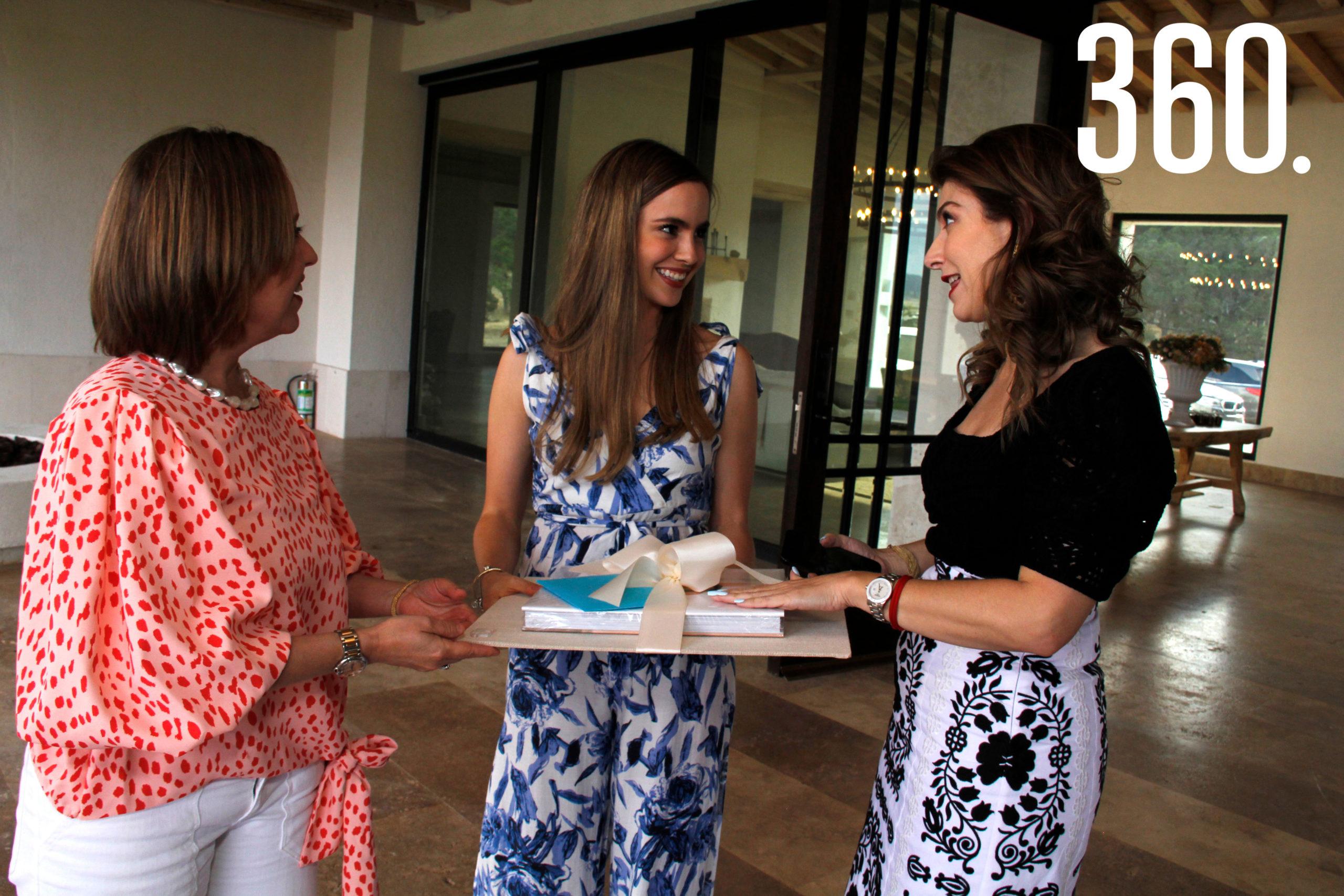 Liana Dávila y Verónica Abramo entregaron el regalo a Daniela, de parte de las organizadoras de la despedida.