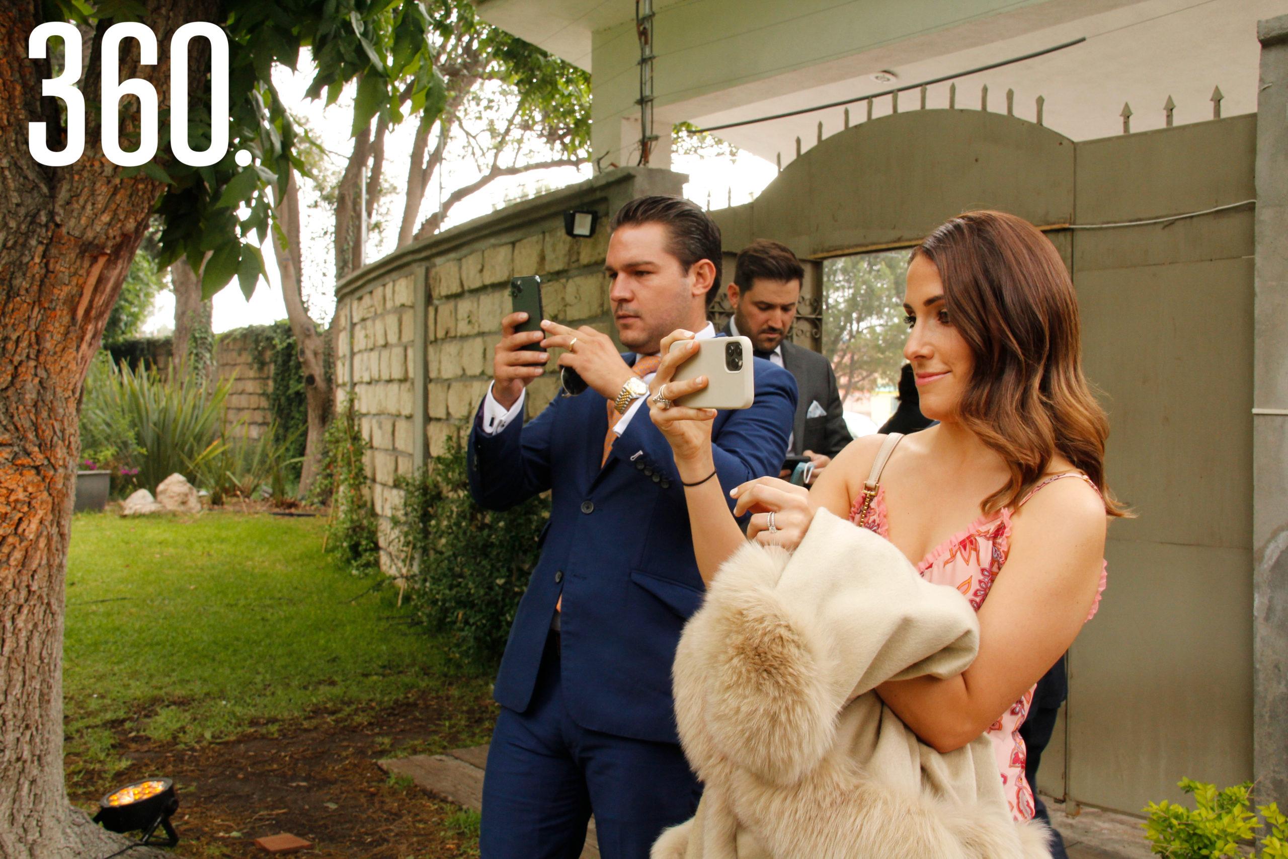 David García y Marcela Cepeda tomando fotos de los novios.