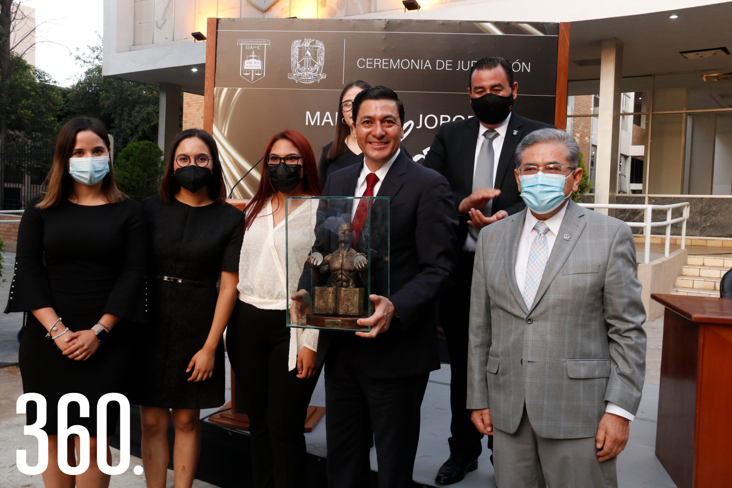 """Un grupo de alumnos entregó al homenajeado una estatua con el lema """"Ubi Jus Ibi Societas"""", junto al rector Salvador Hernández."""
