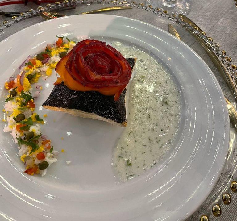 Almohadilla de hojaldre negro con rosetón de salmón.
