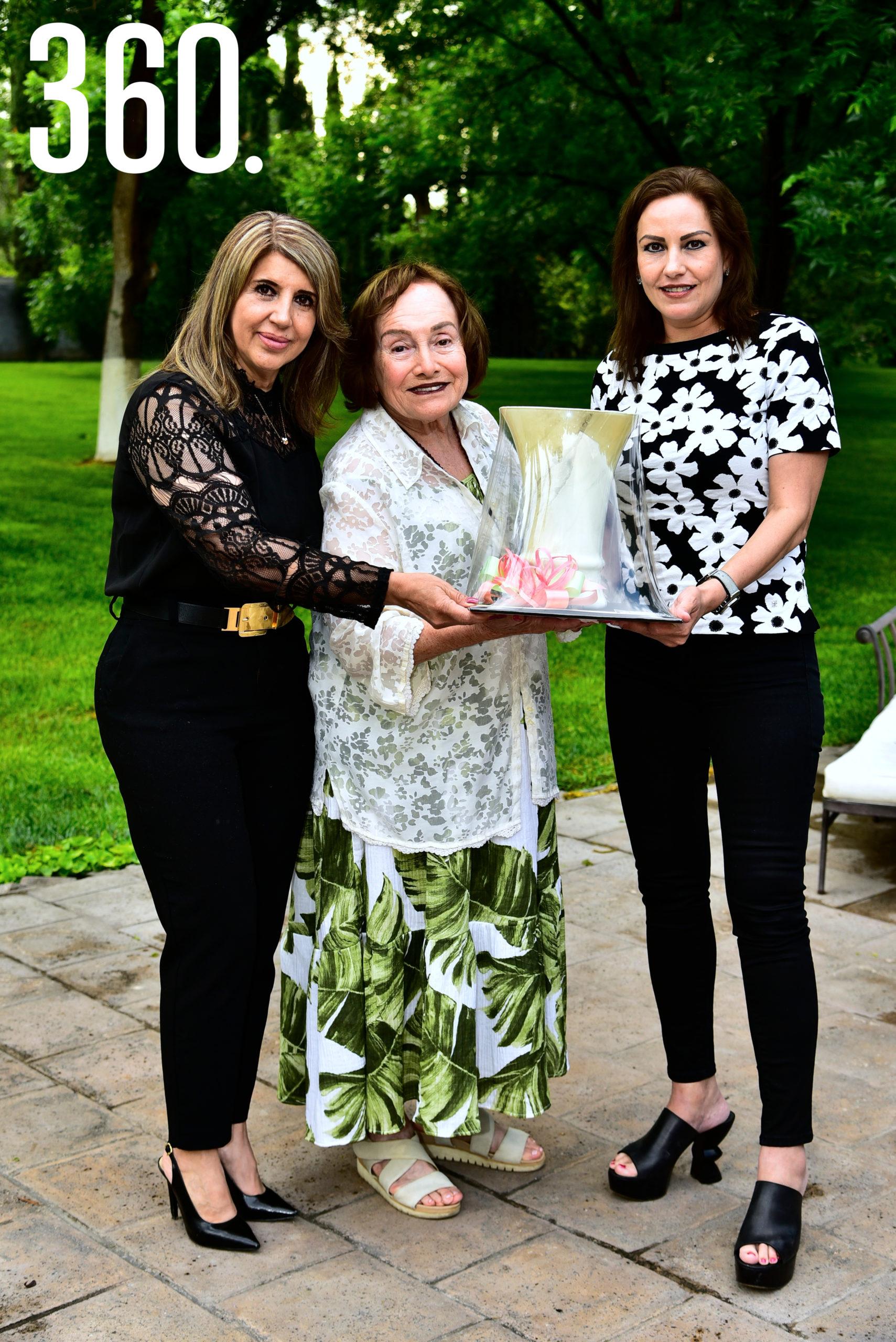 Griselda Valdés y Katia Talamás entregando un regalo a Felisa Fausti de Guerra, una de las socias fundadoras del club Azalea.