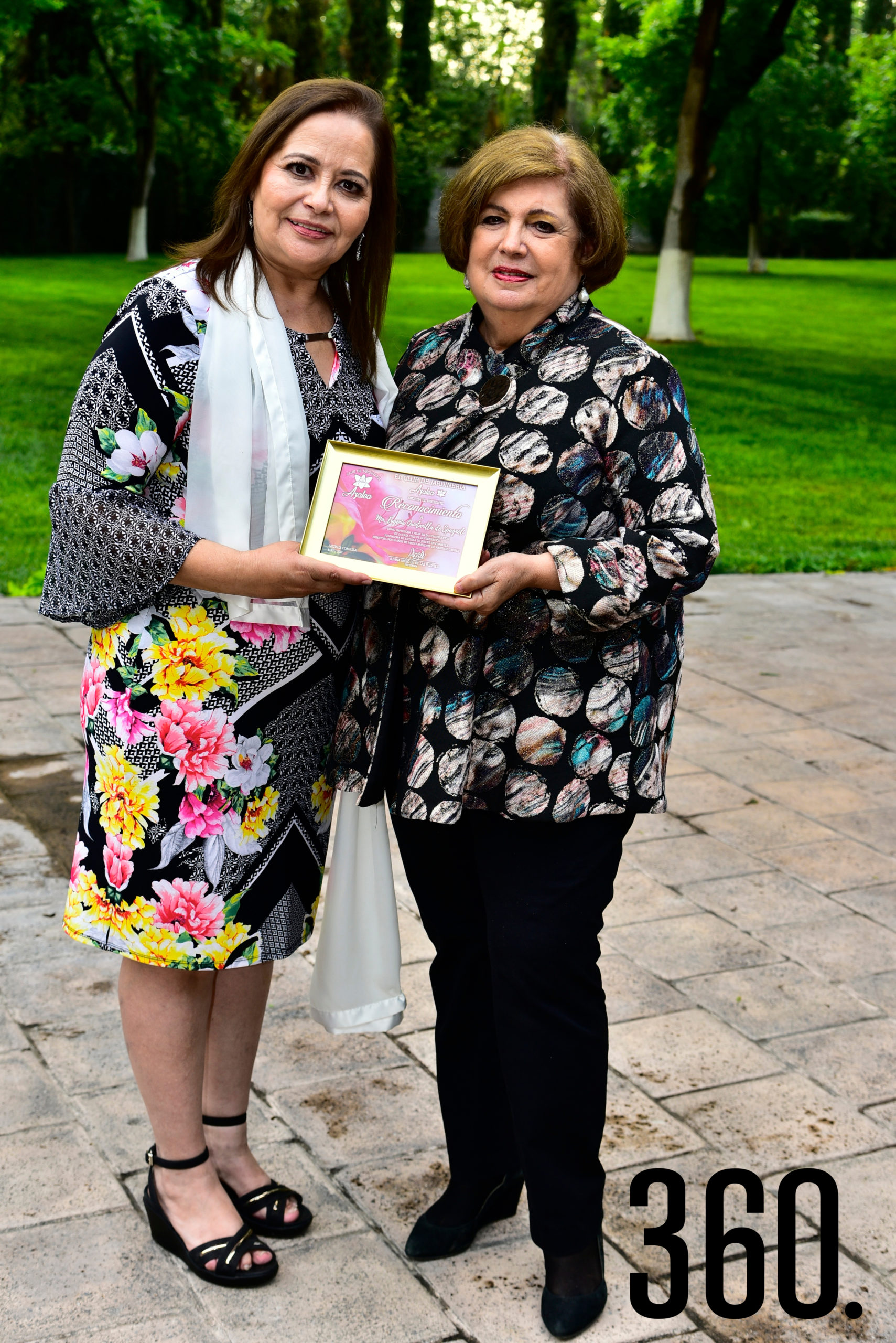 Lili Melo de De las Fuentes entregando un reconocimiento a María Eugenia Quintanilla de Spagnoli.
