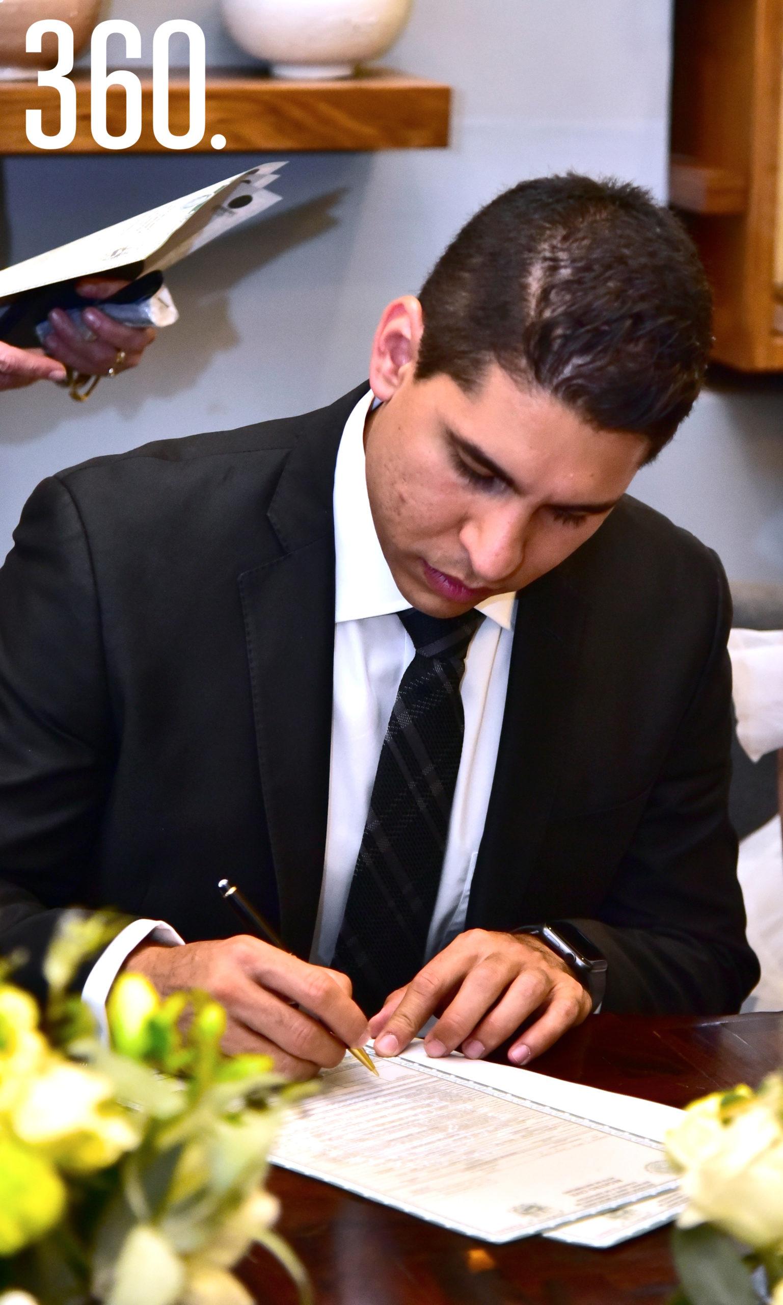 El novio firmando.