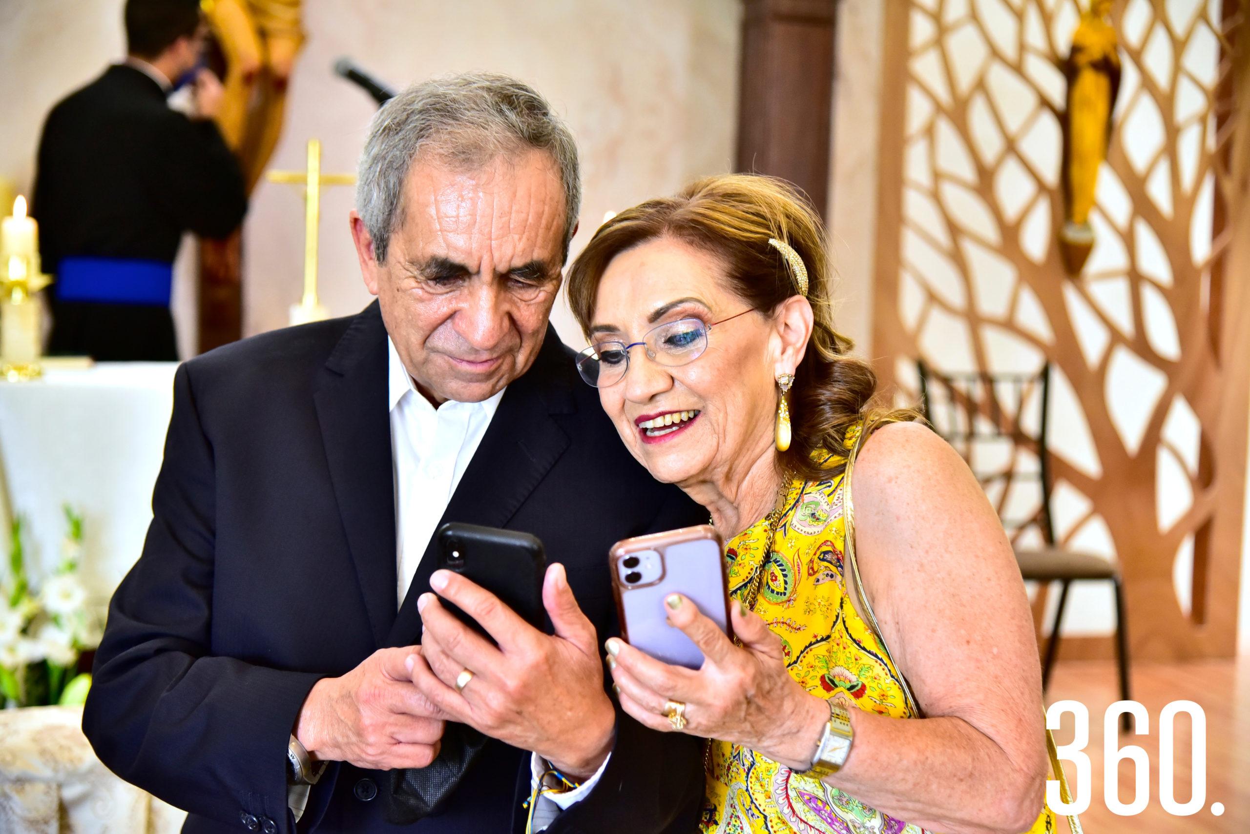 Los festejados viendo sus fotos.