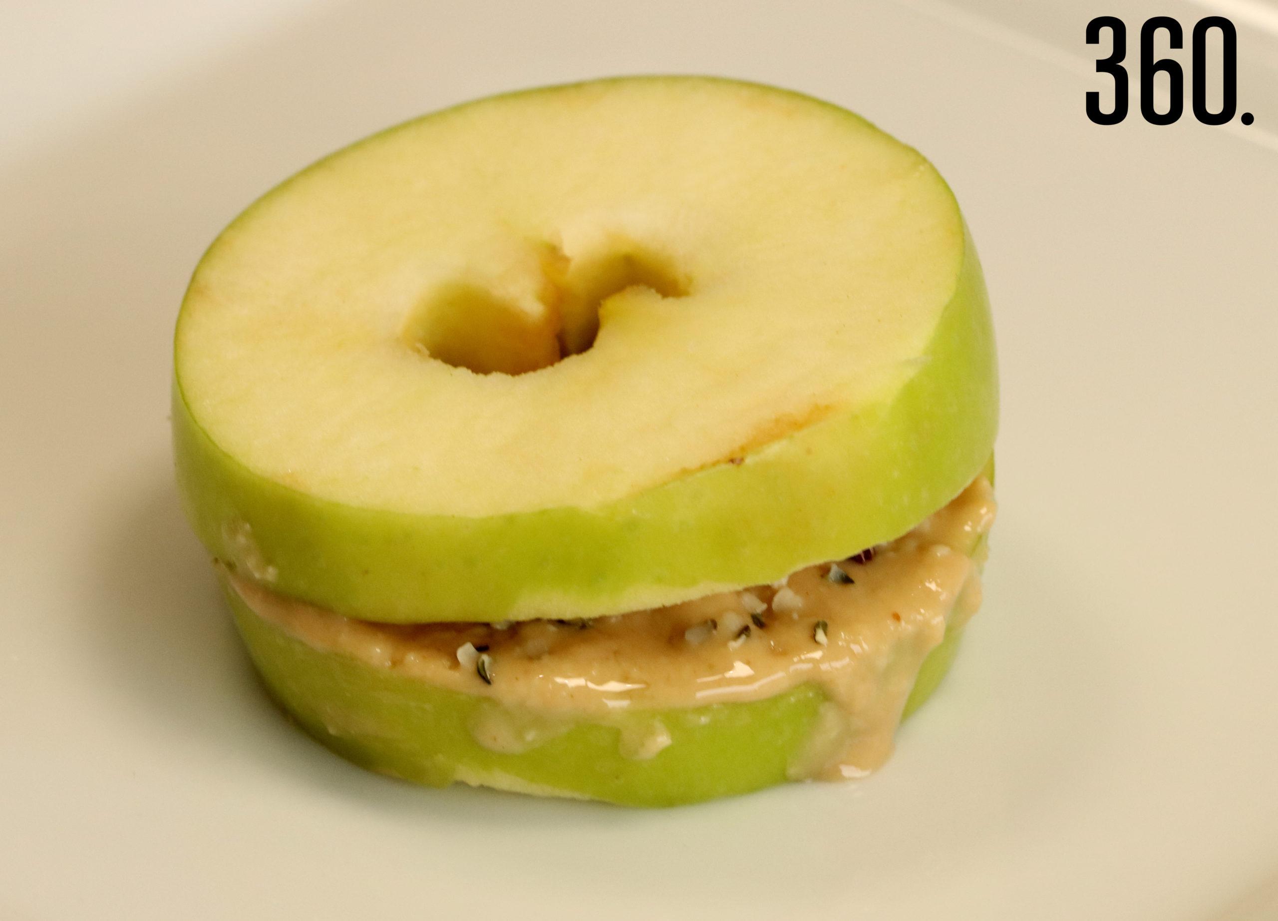 Sandwich de manzana con crema de almendras y cacao.