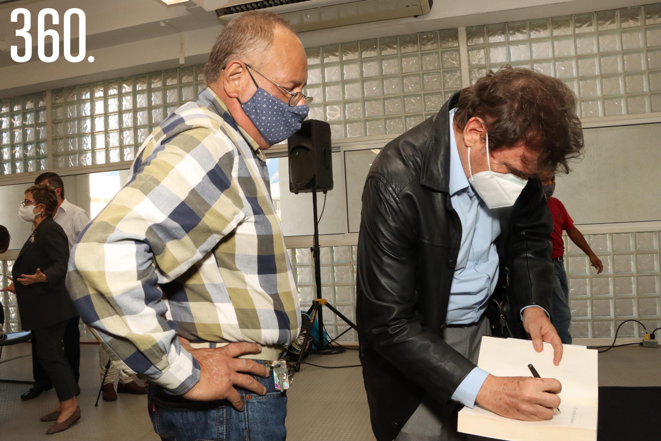 Eduardo Valdés espera la firma del autor Enrique Serna.